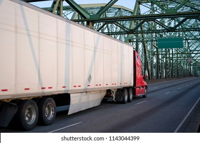 Red big rig long haul semi truck driving alone interstate highway transporting packed commercial cargo in dry van semi trailer moving on arched metal truss green Columbia Interstate Bridge