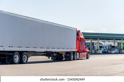 Red big rig long haul powerful semi truck transporting commercial cargo in dry van semi trailer running on the truck stop to fuel station with another trucks for refuel and continue delivery
