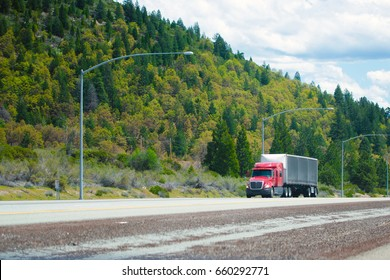 Red big rig modern shiny semi-truck with black tarp dry van trailer with aerodynamic spoiler in front of trailer move on straight divided interstate highway I-5 in Oregon with green trees forest