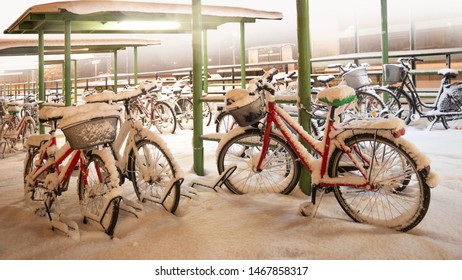Red bike in bicycle park during snow storm