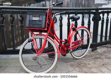 Red bike on bridge over gracht canal, Amsterdam, London