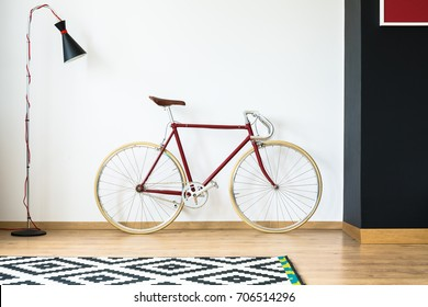 Red bike in simple living room with design lamp and patterned black and white carpet