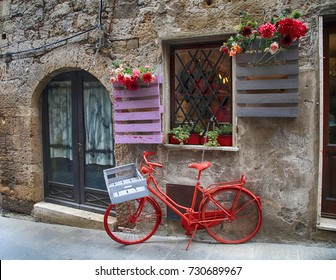 Red bike standing in front of old stone wall in a traditional Italian medieval town, Tuscany, Italy.