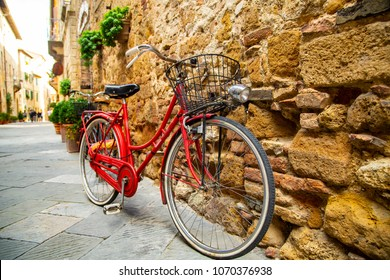 Red bike stop beside the wall in Tuscany Italy.