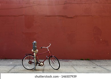 Red biked locked to a parking meter in front of a red painted wall