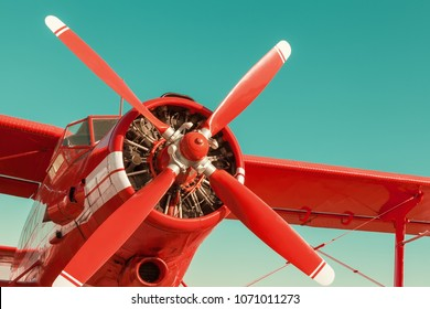 Red biplane on sky background. Close-up with engine and propeller