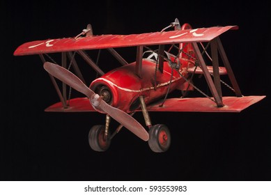 Red biplane replica with black background
