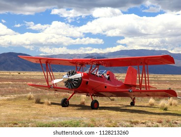 Red biplane waiting for another daredevil