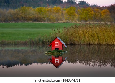 Red bird house on a raft in a quiet pond. There are autumn colors in the background