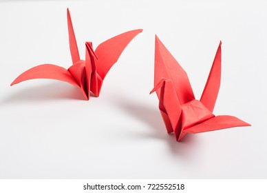Red bird origami on white background.