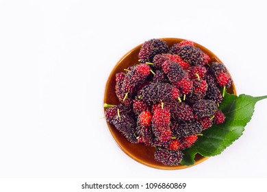 red and black berry fruit and mulberry leaf  in brown bowl on white background healthy mulberry fruit food isolated
