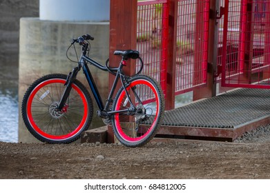 Red and black bike leans against a red metal fencing post under a bridge.