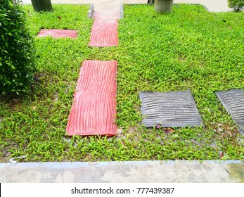 Red and black bricks  blocks like as wood is the footpath amid green lawns in tropical house garden.Beautiful garden decoration design.Concept for house,office garden decorator for create new design