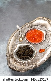 red and black caviar in bowl on a concrete background