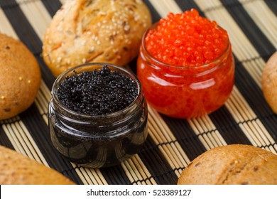 Red and black caviar in a jar with bread