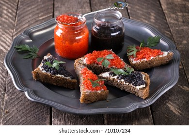 Red and black caviar in small silver spoon on a wood background with black bread ,food concept