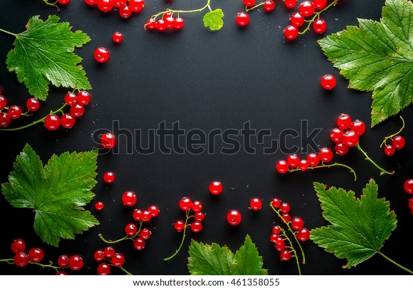 Red And Black Currants With Leaves On A Black Background. Free Space For Text. Top View.