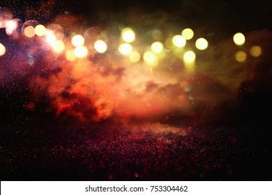 Red, black and gold glitter vintage lights background. defocused.