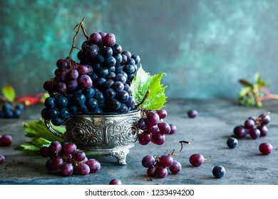 Red and black grapes with grape leaves in a metal bowl on a rustic background. Copy space.
