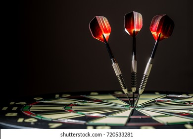 Red, black, and green dartboard on its side with three fiery metal tipped darts in the bulls eye. On black background.