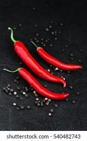 Red and black hot peppers on the black table