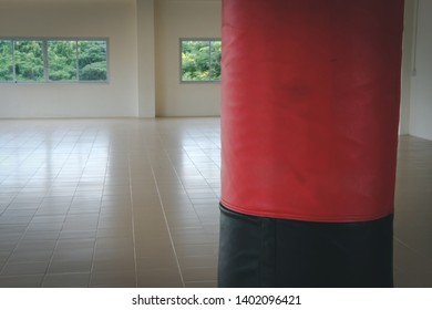 red and black sandbag for hitting and punching in boxing gym. sport, fitness lifestyle concept.