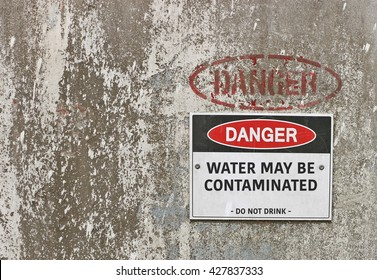 red, black and white Danger, Water May Be Contaminated warning sign