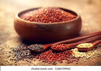 Red, black and white quinoa grains in a wooden spoon. Healthy food in a bowl. Seeds of white, red and black quinoa - Chenopodium quinoa