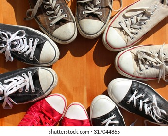 Red, black and white sneakers standing in the circle, view from above
