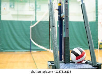 Red, black, and white volleyball and net in a school gymnasium.
