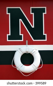 A Red, Black, and white wall with a life preserver.