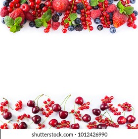 Red and black-blue fruits and berries. Ripe red currants, strawberries, raspberries, blackberries, blueberries, cherries on a white background. Berries at border of image with copy space. Top view