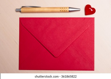 Red blank envelope little heart and pen on wooden surface. Valentine day card, love or wedding greeting concept.