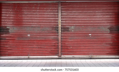 A red blank metal shutter door, with a copy space for text, on a front modern commercial shop. Shop closed theme.