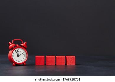 Cubes rouges en bois vierge et réveil sur fond noir, espace pour copie. Concept du temps à la vente. Vendredi noir. Vente nocturne
