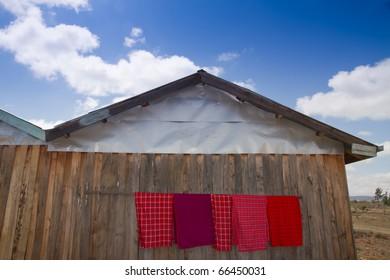 Red blankets for sale outside wooden hut in Masai Mara kenya