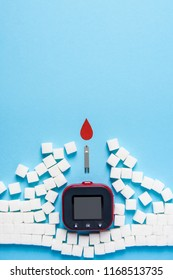 red blood drop and wall made of sugar cubes ruined by Blood glucose test strips and Glucose meter on blue background, world diabetes day. Copy space. Top view