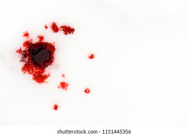 Red blood drops on a white snow background from a hunting injury or crime related scene