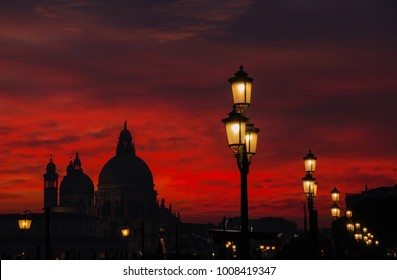 Red blood sky sunset over Venice Lagoon with Salute Basilica domes and lamps