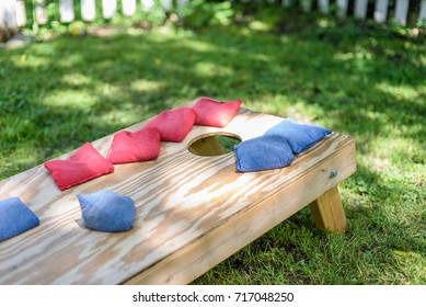 red and blue bags on homemade wood cornhole board