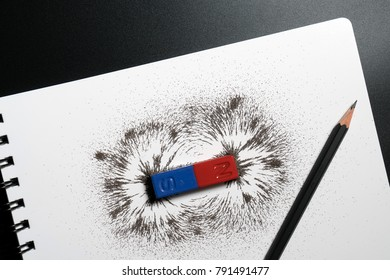 Red and blue bar magnet or physics magnetic, pencil and iron powder magnetic field on white background. Scientific experiment in science class in school.