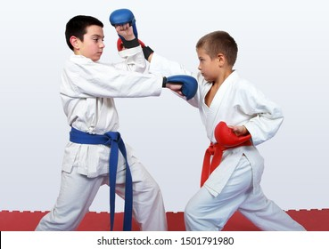 With a red and a blue belt athletes doing paired exercises  karate