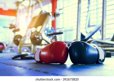 Red And Blue boxing gloves hanging on a Blue wall IN Gym Fitness