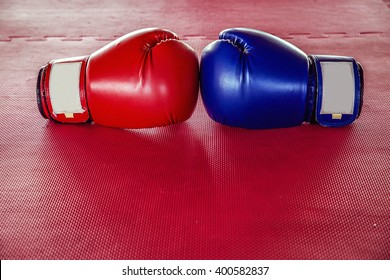 Red And Blue boxing gloves On Red rubber flooring