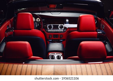 Red with blue cabriolet interior - rear view. The red head restraints of the four seats, front panel of the car, part of the steering wheel, front doors and a windshield with a rear-view mirror. - Shutterstock ID 1936521106