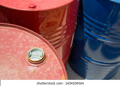 Red and blue chemical storage tanks. Barrels for shipment from stock. Transport of hazardous liquids. Warehouse work. Chemical industry.