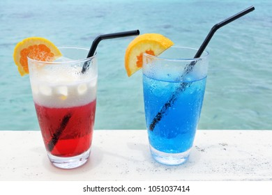 A red and blue cocktail drinks with ice served on a poolside table in a tropical resort.Travel holiday vacation food and beverages concept. Copy space