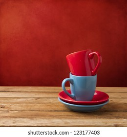 Red and blue coffee cups on wooden table over red grunge wall