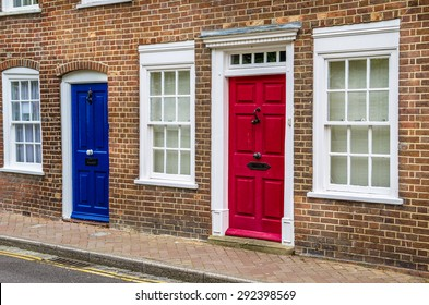 Red and Blue Front Doors and White Windows on a Terraced House in UK. Traditional British Doors.