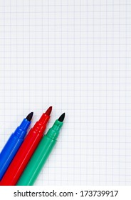 Red, blue and green markers on background of graph paper